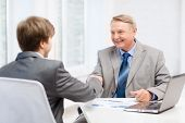 business, technology and office concept - older man and young man shaking hands in office