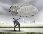 Powerful businessman holding huge stone above head