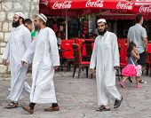 SARAJEVO, BOSNIA AND HERZEGOVINA - AUGUST 13, 2012: Group of religious Muslim men walk on street close to main mosque in old town Sarajevo.