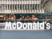 SARAJEVO, BOSNIA AND HERZEGOVINA - AUGUST 11, 2012: Tourists and local teens having their meals at McDonald's, looking out at street.