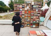 SARAJEVO, BOSNIA AND HERZEGOVINA - AUGUST 11, 2012: Woman perusing bookshelves on street market, com