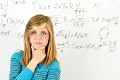 Desperate student girl standing in front of mathematics board