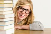 Cheerful student teenager looking from behind stack of books glasses