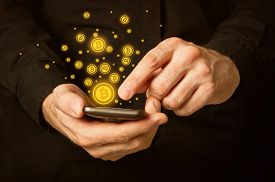 foto of bit coin  - Hand holding smart phone mobile with bitcoin currency symbol - JPG