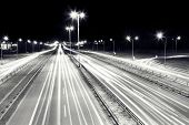 Highway traffic at night. Cars lights in motion on the streets. Transport, transportation industry