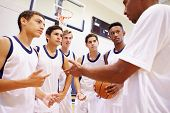 stock photo of 16 year old  - Male High School Basketball Team Having Team Talk With Coach - JPG