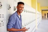 picture of 16 year old  - Male High School Student By Lockers Using Mobile Phone - JPG