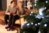 Couple Exchanging Gifts By Christmas Tree
