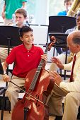 stock photo of orchestra  - Boy Learning To Play Cello In High School Orchestra - JPG