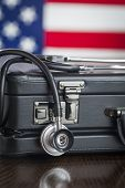 Leather Briefcase and Stethoscope Resting on Table with American Flag Behind.
