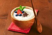 natural samolina pudding with fresh blueberries and strawberries, served in a ceramic bowl with wood