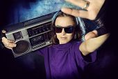 Portrait of a modern girl with tape recorder over grunge background. Street urban style.