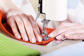 stock photo of neat  - Neat tailor sewing orange fabric very precisely - JPG
