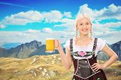 Beautiful Bavarian woman holding a pint of beer somewhere high in the mountains