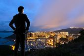 Asian businessman standing in the hill and looking at the skyscrapers and harbor in Aberdeen, Hong K
