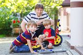 Father And Two Little Sibling Boys Reparing Broken Bicycle