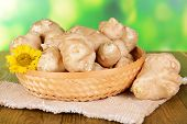 Topinambur roots in wicker basket on table on bright background