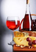 Pink wine, grapes and cheese on grey background
