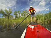 senior male paddler enjoying workout on stand up paddleboard (SUP), calm lake in Colorado, spring co