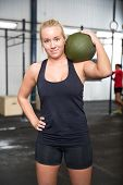 pic of slam  - Attractive young girl rests with a slam ball on the shoulder after workout at a fitness gym center - JPG