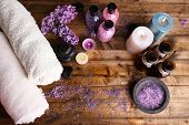 Composition with spa treatment, towels and lilac flowers, on wooden background