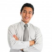 Portrait of handsome Asian young man in casual business attire, smiling confidently with arms crossed, standing isolated on white background.