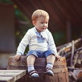 little boy sits on barrel in the village