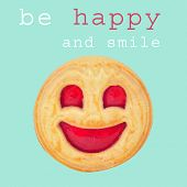 a biscuit with a smiley biscuit and the sentence be happy and smile on a blue background