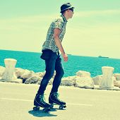 a young man roller skating near the sea, with a cross-processed effect