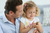 Man with 3-year-old girl playing with smartphone