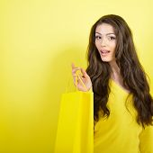 Shopping happy young woman holding bags over yellow studio background.