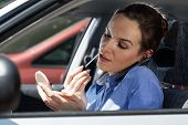 Pretty Woman In A Car Doing Makeup While Standing In A Traffic Jam