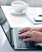 Woman hands typing on laptop