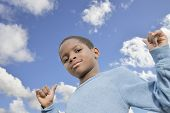 Young Afro boy, blue sky and sunny day
