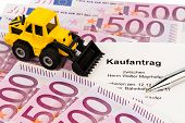 the purchase contract for a new excavator. with euro money and pen