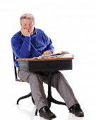 A mature sitting in an old school desk looking bored.  On a white background.