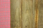 Red checkered (gingham) border on rustic wooden background