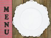 Menu sign on red checkered napkin with empty white plate against rustic wooden table