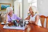 Two retired older women sitting together having tea and muffins and laughing