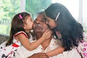 Portrait Indian family at home. Grandchildren kissing on grandparent face. Asian people living lifes