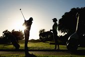 foto of take off clothes  - Golfing couple teeing off for the day on a sunny morning at the golf course - JPG