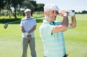 picture of swing  - Golfer swinging his club with friend behind him on a sunny day at the golf course - JPG