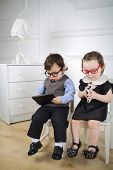Little children sitting on white chairs: boy in black glasses with tablet computer and girl in red glasses with mobile phone