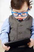 Serious little boy in blue glasses holding tablet computer in hands