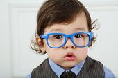 Portrait of serious little boy with big brown eyes and blue glasses
