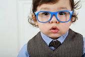 Portrait of serious small boy with big brown eyes and blue glasses