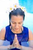 Beautiful woman with frangipani flowers in her hair, praying pose in swimming pool
