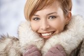 Closeup portrait of attractive young woman wearing warm fur coat in winter.