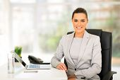 happy young business woman sitting in office