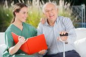 stock photo of nursing  - Portrait of happy senior man sitting by female nurse holding book at nursing home - JPG